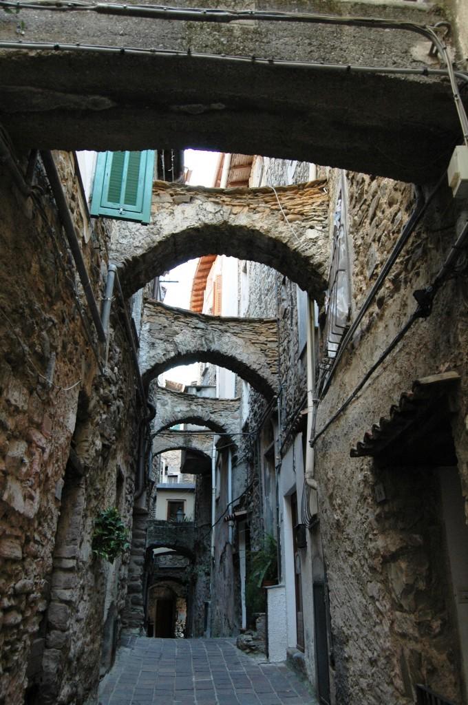 """Soldano (IM), estremo ponente di Liguria, nella valle del torrente Verbone, lungo la strada che porta, passando anche da S. Biagio della Cima, da Vallecrosia a Perinaldo; oggi comune, ma già """"villa"""" staccatasi - come già sottolinrato per S. Biagio della Cima - , con l'assenso di Genova, da Ventimiglia per dare vita, alla fine del XVII secolo, con le altre alla Magnifica Comunità degli Otto Luoghi, irripetibile esempio, a quei tempi, di democrazia e non solo"""