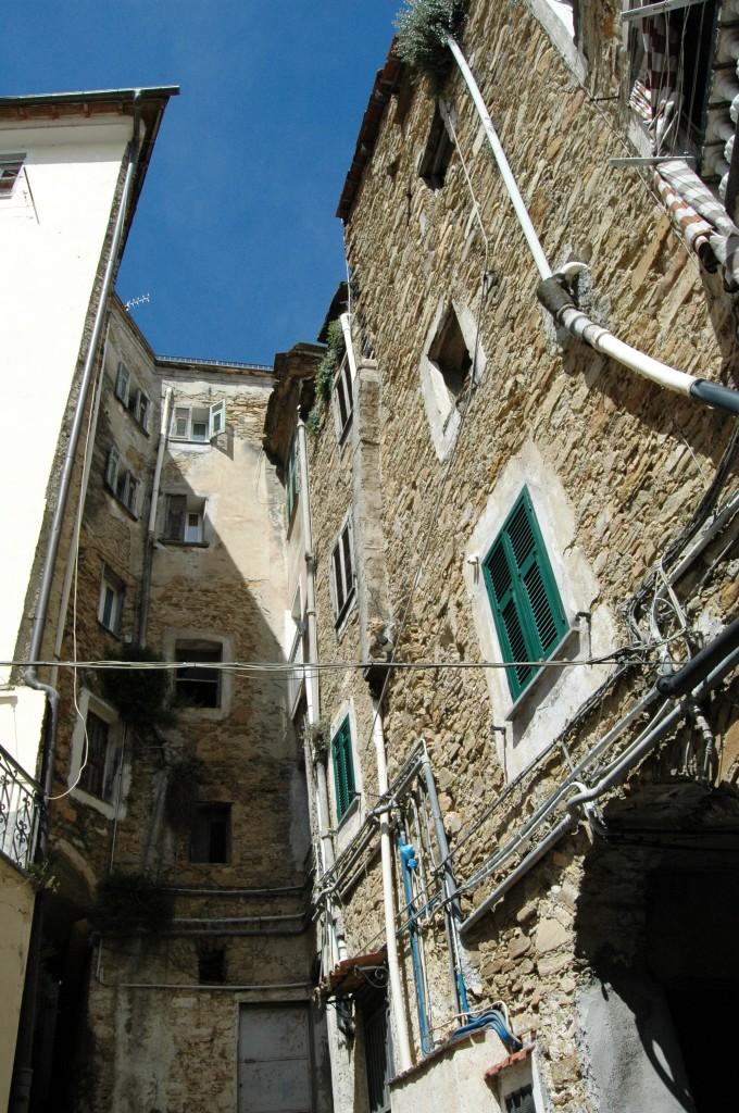 """San Biagio della Cima (IM), estremo ponente di Liguria, nella valle del torrente Verbone, lungo la strada che porta, passando anche da Soldano, da Vallecrosia a Perinaldo; oggi comune, ma già """"villa"""" staccatasi, con l'assenso di Genova, da Ventimiglia per dare vita, alla fine del XVII secolo, con le altre alla Magnifica Comunità degli Otto Luoghi, irripetibile esempio, a quei tempi, di democrazia e non solo; borgo natio di degni scrittori, tra cui Francesco Biamonti."""